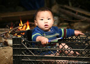 Baby boy sitting in a crate in Sapa Vietnam