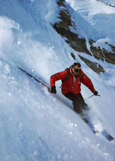 Man skiing off piste on steep mountain