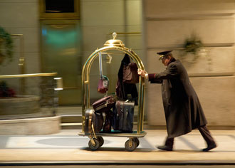 Hotel porter pushing trolley full of luggage