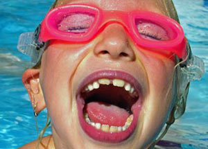 Young kid with goggles smiling in a swimming pool