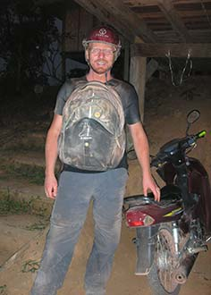 Man standing next to motorcycle driving the Laos Loop