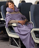 Woman sitting on airplane with travel blanket wrapped around her