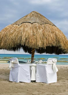 Decorated luxury dining table for two under beach umbrella