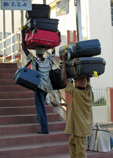 Men carrying too much carry on luggage