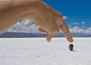 Finger pointing at rock in a desert