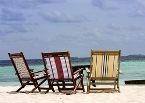 Three beach chairs on sunny beach