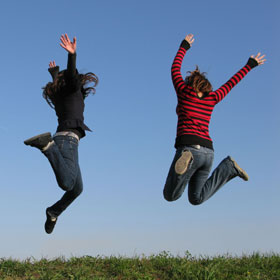 Two travelling teenagers jumping in the air