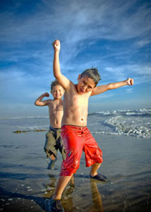 Two young boys dancing on the beach
