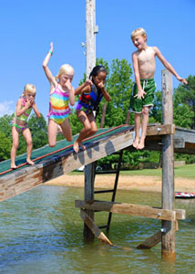 Four children jumping off a small bridge into a water