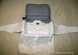 Shirt layed over carryon luggage as first part of bundle wrapping packing