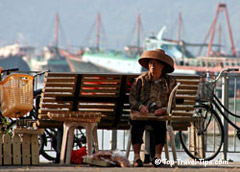Elderly woman with hat sitting on a bench in Vietnam