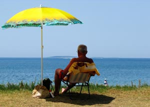 Man sitting under sun umbrella