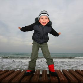 Young child making flying gesture on a seafront pier